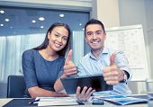 business, people, technology and teamwork concept - smiling businessman and businesswoman with table poster
