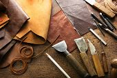 Leather craft or leather working. Leather working tools and cut out pieces of leather on leather cra poster