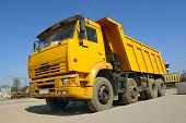 picture of dump_truck  - Yellow dump truck parked against clear blue sky - JPG