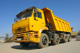 image of dump_truck  - Yellow dump truck parked against clear blue sky - JPG