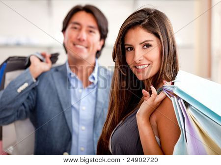 Beautiful shopping couple at a store holding bags and smiling