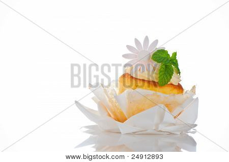 Cupcake With Vanilla Cream Mint Leaf And Sugar Flower On A White Background