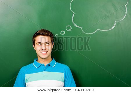Man standing next to thought bubble on blackboard