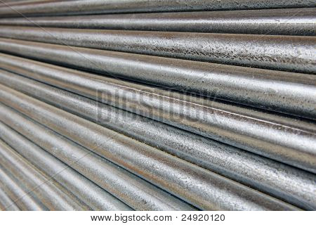 Pile of shiny galvanized steel pipe diminishing from right to left