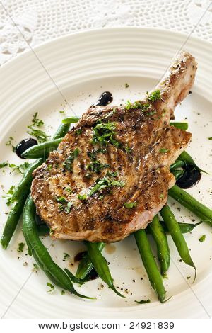 Grilled pork loin cutlet over green beans.