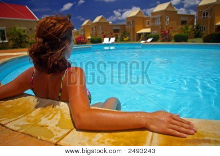 Woman Sitting By Edge Of Pool