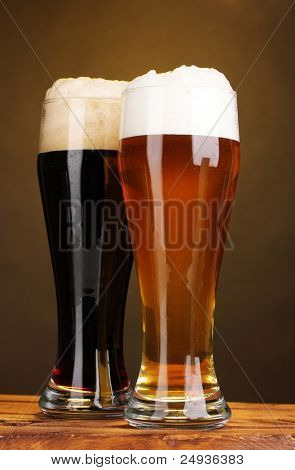 black and golden beer in glasses on wooden table on brown background