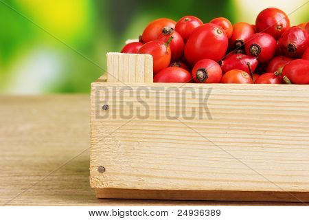 ripe briar in wooden box on wooden table on green background