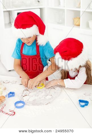 Kids making christmas cookies cutting the dough