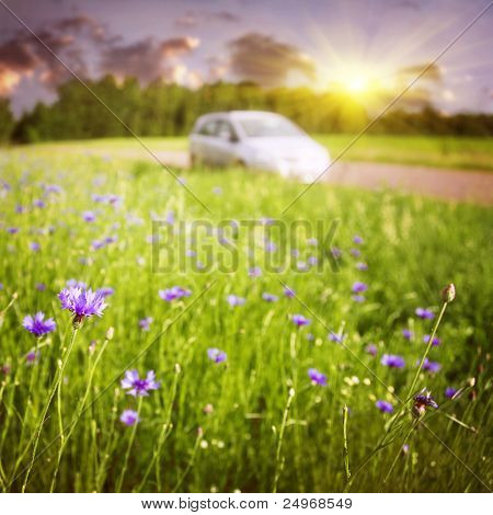 Zonsondergang landschap met auto op achtergrond.