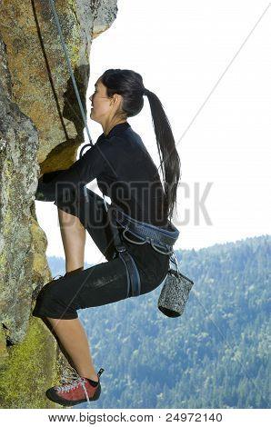 Pretty Young Woman Rock Climbing
