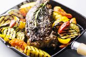 Greek Organic Lamb Steak With Grilled Vegetables And Herbs In Sizzling Skillet poster