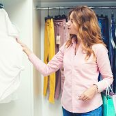 Smiling Elegant Woman Choosing Clothes In Luxury Store. Sale, Consumerism, And People Concept. Girl poster