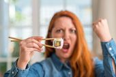 Redhead woman eating sushi using chopsticks annoyed and frustrated shouting with anger, crazy and ye poster