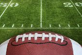 pic of football  - A photo of an American Football with the focus on the leather texture and laces or threads with a football field in the background - JPG