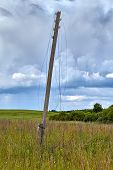 Wooden Electric Pylon In Summer Field De-energized Wires Are Broken And Hanging In Air, Power Failur poster