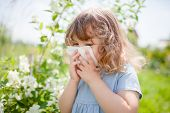 Allergy Concept. Little Girl Is Blowing Her Nose Near Blooming Tree. Allergy To Flowers. poster