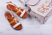 Fashionable Womens Sandals And Backpack On White Wooden Background poster