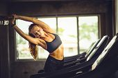 Young Woman Attractive Fitness Exercise Workout In Gym. Woman Stretching The Muscles And Relaxing Af poster