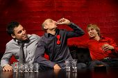 stock photo of bachelor party  - Men drinking shots in night club - JPG