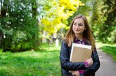 Portrait Of Smiling University Student Standing In The Park On Her Way To Class. Girl Is Wearing A B poster
