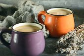 In A Small Orange Mug Coffee With Milk. Near The Purple Mug And Dry Lavnd. Beautiful Still Life. poster