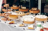 Delicious Cakes And Pie With Whipped Cream On Table At Street Food Festival. Candy Bar With Tasty Sw poster