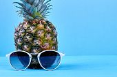 Realistic Ananas With Sunglasses And Copy Space. Pineapple And Sunglasses On Blue Background With Te poster