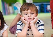 Boy Kid Lay Down On Library Floor With Bored Feeling In Preschool Library,kindergarten School Educat poster