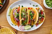 tasty mexican tacos with beef fajita filling served with salsa and guacamole in flat lay composition poster