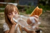 Portrait Of Poor Thirsty Homeless Girl Drinking Water From Plastic Bottle In The Dirty Alley, Select poster