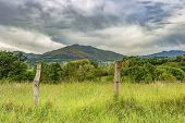 French Pyrenees Mountains Rural View Behind Agricultural Fencing, Dramatic Overcast Sky, Leaving Sai poster