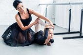 Young Ballet Teacher And Cute Little Student Exercising Together In Ballet School poster