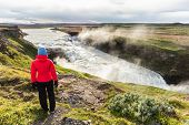 Iceland travel Gullfoss waterfall tourist woman looking over icelandic falls, famous attraction on t poster