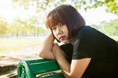 Young Asian Woman Sitting Outdoor On The Public Bench And Lying Along The Bench In The Park In Warm  poster
