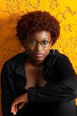 Teenage African American Girl With A Short, Red Afro Sits In Front Of A Bright Orange, Stucco Wall.  poster