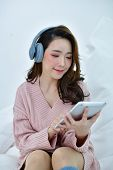 Winter Concept. Cute Asian Girl In Winter Dress. Beautiful Women In Winter Clothes Are Listening To  poster