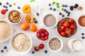 variaty of raw cereals, fruits and nuts for breakfast. Oatmeal flakes and steel cut, barley, walnut, poster