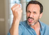 Handsome middle age man annoyed and frustrated shouting with anger, crazy and yelling with raised ha poster