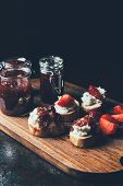 Close Up Shot Of Jars With Jam, Sandwiches With Cream Cheese, Strawberry Slices And Fruit Jam On Cut poster
