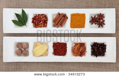 Spice collection of chili flakes, cinnamon, turmeric, star anise, nutmeg, ginger, saffron, mace, cloves and bay leaf herb in white porcelain dishes over hessian background.