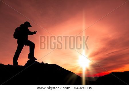young man using smart phone on the top of mountain