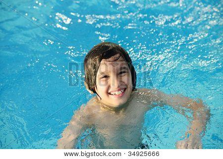 Little happy boy on pool
