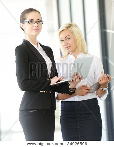 Two business women standing with a tablet in their hands