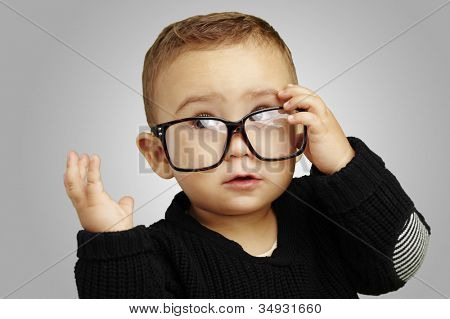 portrait of a serious kid wearing glasses and doing a gesture over a grey background