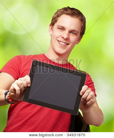 portrait of a young man holding a digital tablet against a nature background
