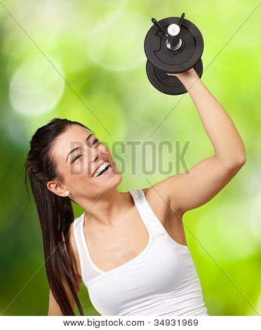portrait of a young girl training with weights against a nature background