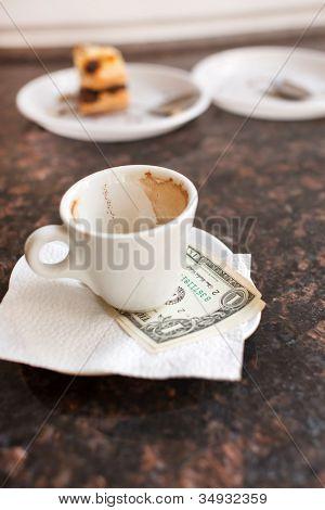 dollar bills under a coffee cup