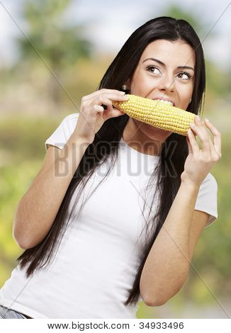 woman eating a delicious corncob, outdoor