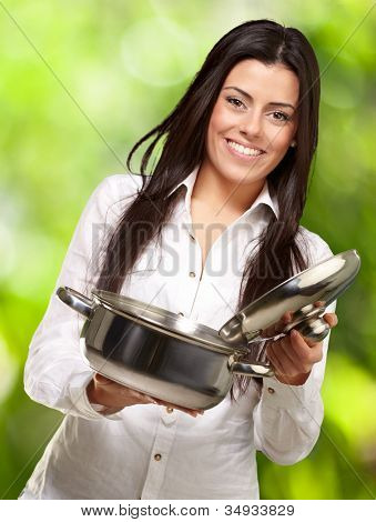 portrait of a young girl opening a sauce pan against a nature background